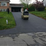 Worker on paving vehicle for driveway