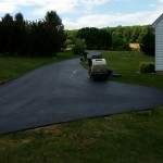 Large driveway winding towards woods