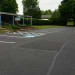 Large parking lot paved with parking spots and handicap spots marked