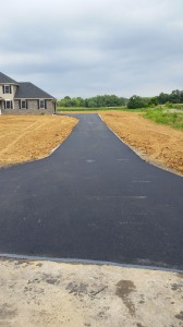 Long driveway leading up to garage of house