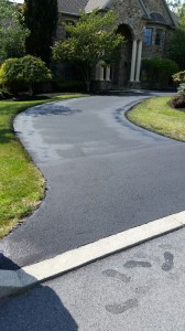 Curved driveway leading up to large stone house