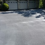 Wide driveway paved towards three car garage