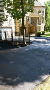 Paved driveway leading up to elegant stone house