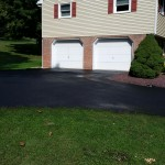 paved driveway leading up to garage doors of house