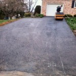 Paving contractor using equipment to pave driveway
