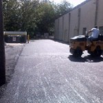 Steam roller flattening driveway after paving