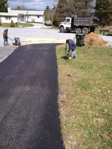 Worker using cleaning equipment on driveway to remove dirt after paving