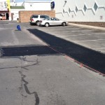 Patched pavement in parking lot roped off