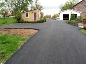 Long driveway paved leading up to shed and garage