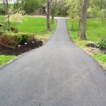 long driveway with landscaping elements on either side