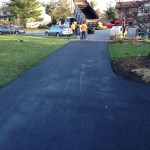 Workers preparing vehicles after paving driveway