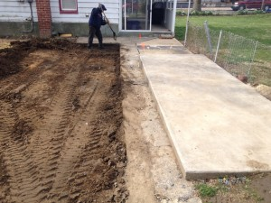Mark's Paving contractor digging flat surface by hand with shovel
