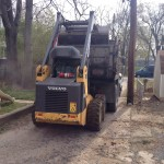 Skid steer pouring dirt into back of truck