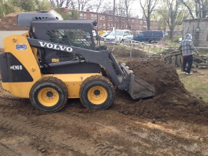 Contractor using skid steer to push dirt for flat surface