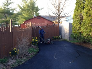Paving contractor adding finishing touches to driveway after paving