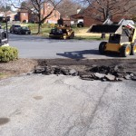 Contractor using skid steer to remove old damaged driveway