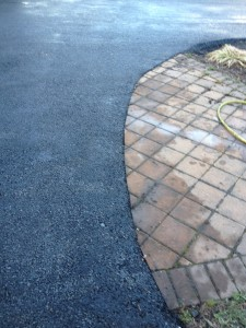 closeup of curved driveway around stone patio
