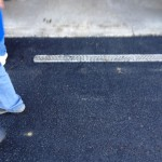 Closeup of paving up to garage and around thin grate