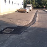 Line of damaged parking lot patched over