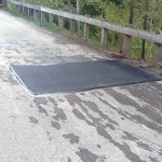 Side of road with potholes patched over with fresh pavement