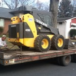 closeup of skid steer being unloaded at paving site