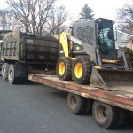 Skid steer being transported to home for excavating
