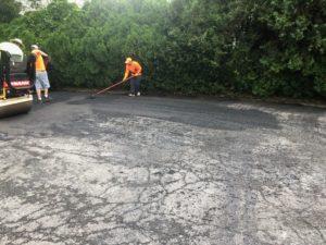 man shoveling asphalt