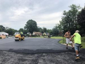 three men working on paving alot