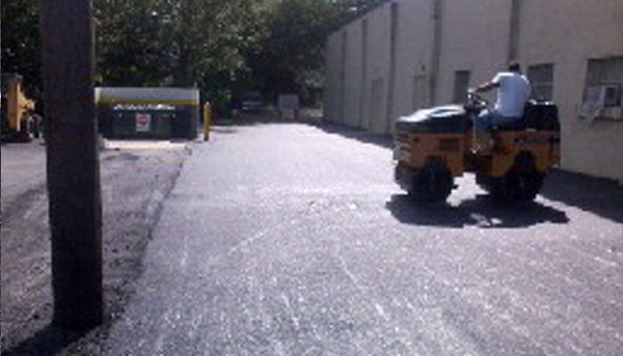 paving contractor steamrollingparking lot